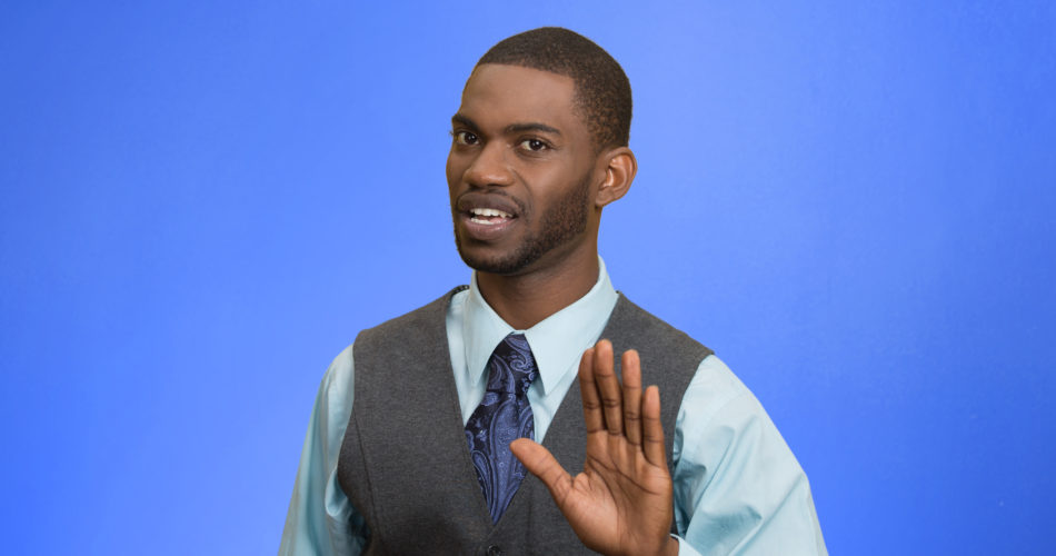 Closeup portrait furious angry annoyed displeased young man raising hands up to say no stop right there isolated blue background. Negative human emotion facial expression sign symbol body language